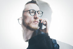 Double exposure bearded banker wearing black shirt and glasses, holding contemporary smartphone hand. Isolated white, portrait man Stock Photos