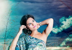 Double exposure of beautiful young woman on a background of sky and clouds expressing purity and freedom. Stock Images