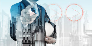 Double exposure of business engineer press play. Button sign to start or initiate projects and abstract city Royalty Free Stock Photos