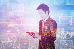 Double exposure of business man using smart phone with city back royalty free stock photos