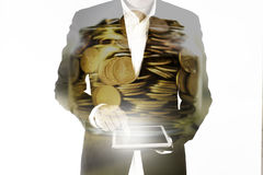 Double exposure of The business man is working on the tablet and golden coins in jar, investment assistance concept Stock Image