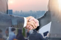 Double exposure of Business people handshake wearing suits on building royalty free stock photos