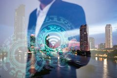 Double exposure of business, technology and internet connection concept. Businessman using icon wifi on hand and modern city royalty free stock photography