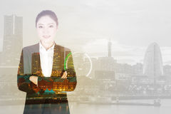 Double exposure of  business woman crossed arms with city backgr Stock Photos