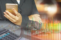 Double exposure of business woman hand holding smart phone , pile of coins, financial graph. Stock chart and calculator in background Stock Photos
