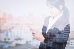 Double exposure of business woman using smart phone with blur city stock photos