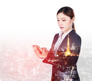 Double exposure of business woman using smart phone with city ba stock photos