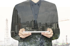 Double exposure business worker holding tablet with city Royalty Free Stock Image