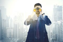 Double exposure of businessman with binocular. Double exposure of young businessman looking through binoculars with modern city background Stock Photo