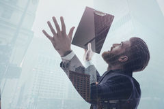 Double exposure with businessman and city view. Longing for success. Inspired male manager is looking at urban skyscrapers and gesturing with excitement. He is Royalty Free Stock Photos