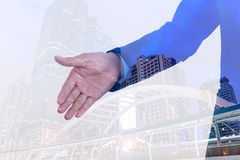 Double exposure of Businessman extending hand to shake with city background Royalty Free Stock Images