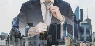 Double exposure businessman holding neck tie with modern buildings in Bangkok city background. S Stock Images