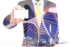 Double exposure of Businessman holding or showing blank business card and city background Stock Photo