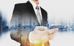 Double exposure businessman holding smartphone with telecommunication towers and modern buildings in sunrise, business network com Royalty Free Stock Photography