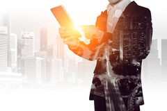 Double exposure of businessman holding tablet with cityscape blurred background. Double exposure of businessman holding tablet with cityscape blurred background Royalty Free Stock Images