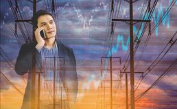 Double exposure Businessman holds tablet, with electric pole, and sky stock graph background, concept of volatility of stocks and royalty free stock photography