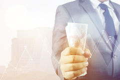 Double exposure of Businessman with money in hand with cityscape Stock Photo