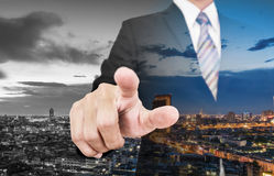Double exposure businessman pointing finger to screen with skyscraper city view Royalty Free Stock Photos