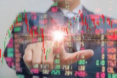 Double exposure of businessman pushing on touch screen with stock market exchange over trading room royalty free stock photography