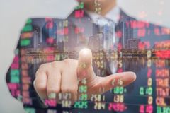Double exposure of businessman pushing on touch screen with stock market exchange over trading room royalty free illustration