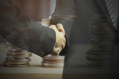 Double exposure businessman shaking hand and money coins, concept in corporate and communicate to success and negotiate royalty free stock photos