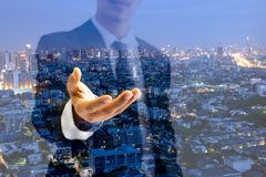 Double exposure businessman stretch hand out with modern buildings royalty free stock photo