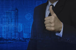 Double exposure of businessman with thumbs up on city and graph. Business Stock Photos