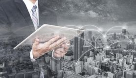 Double exposure businessman using digital tablet, and cityscape. Business network, blockchain technology and internet connection royalty free stock images