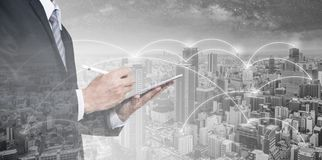 Double exposure businessman using digital tablet, and cityscape. Business network, blockchain technology and internet connection royalty free stock photos