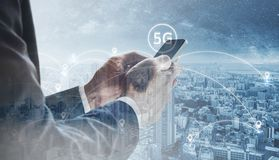 Double exposure, Businessman using mobile smart phone with cityscape and 5G sign royalty free stock photography