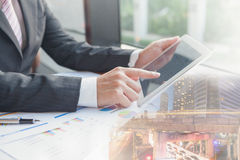 Double exposure businessman using the tablet in office. Stock Photo