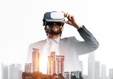 Handsome businessman in rays of sunrise experiencing impressive virtual reality royalty free stock photography
