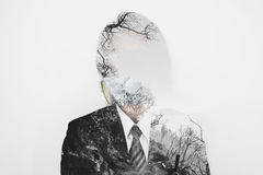 Double exposure, businessman wearing toxic protection mask with dead trees environment, concept of pollution and global warming royalty free stock image