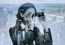 Double exposure of businesswoman with binocular and megalopolis Stock Image