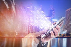Double exposure of city and businessman standing touch the screen on smartphone. concept working online, by email. Royalty Free Stock Photography
