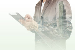 Double exposure of city and Businessman use Tablet device Stock Images
