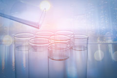 Double exposure of city and pipette adding of several test tubes, medical glassware Royalty Free Stock Image