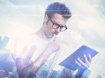 Double exposure of city and young man with tablet Royalty Free Stock Photography