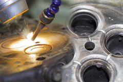 Double exposure close up automobile engine head cylinder repair or modify by welder with laser welding method.  stock photo