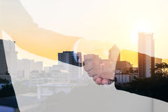 Double exposure closeup of businessmans handshake on city background Royalty Free Stock Images