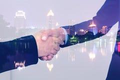 Double exposure closeup of businessmans handshake on city background Stock Photography