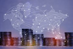 Double exposure of coin stack with city background and world map, financial graph, world map and global network business concept royalty free stock image
