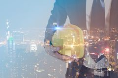 Double exposure concept of engineer with safety yellow helmet for workers security with modern city night background. industry Stock Photos