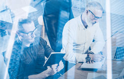 Double exposure concept.Teamwork process in modern coworking studio.Young bearded man and adult businessman making notes Royalty Free Stock Image