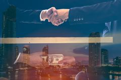 Double exposure of corruption concept two businessman sealing the deal with a handshake and receiving a bribe money. On modern city black background. Hands stock photos
