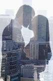 Double exposure of couple kissing over cityscape, side view, silhouette Stock Photo