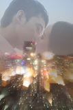Double exposure of couple kissing over night cityscape Stock Image