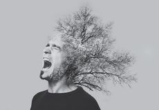 Double exposure emotional screaming man, trees, isolated on grey. Black and white photo.  Royalty Free Stock Image