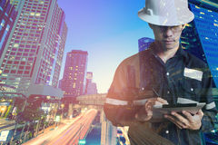 Double exposure of  Engineer or Architecture man in working shir. T and safety helmet working with tablet in night building background , business and Stock Image