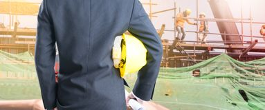 Double exposure Engineer with safety helmet on construction site. Workers Stock Image
